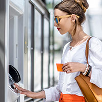 Women in sunglasses using an ATM.